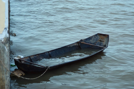 A small boat is tied to a pier. It is half-filled with water, and covered with rust. The water is calm.