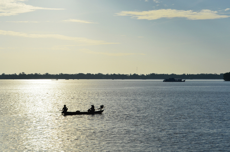 Two fishermen are in a small boat with an outboard motor. They are silhouetted against the late afternoon sun. A few other boats are on the river. The sky is pale blue with white clouds.