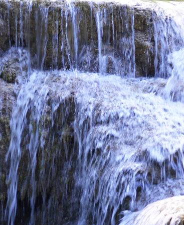 Clear water of a waterfall is tumbling down over brown rocks. A long exposure has made the water look like a flowing sheet of blue-white, with drops of water visible as small white arcs.