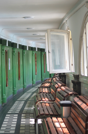A row of wooden benches run beneath a set of windows. Opposite are green doors, leading to change rooms. The floor is decorated with grey and white tiles.