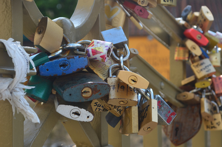 Paddlocks have been locked onto a love-lock bridge. The padlocks are of many colours, with dates and names written on them. Stock Photo