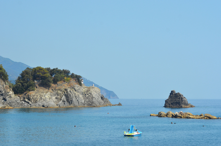 A paddle boat is in a bay which joins the open sea. The water is blue and calm, and the sky is clear. A rocky headland is covered with trees, while other rocks are in the water. A few people can be seen swimming. Stock Photo