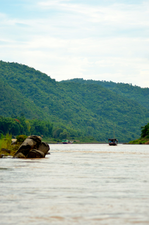 Two wooden boats are on the Mekong in Laos. The water is muddy. On either side are hills covered with forest. Some rocks are in the foreground. Stock Photo