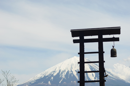 A wooden bell tower, shapped like a ladder, is seen against Mt Fuiji, Japan. A metal bell hangs from the tower. The sky is overcast, with white storm clouds to one side of the mountain.