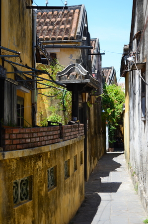 A yellow wall runs down a side street in Hoi An, with an arch over a gate. Yellow old buildings and trees line the street. The sky is blue. The street is deserted. Stock Photo
