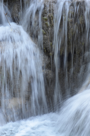 A waterfall flowing over brown rocks caught in slow motion so the falling water aooears blurred and solid. The water falls into a pool  of white water. Stock Photo