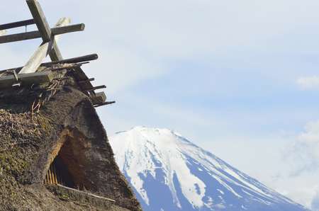 A traditional Japanese thatched roof building. The summit of Mt Fuji rises behind, against a blue sky filled with clouds. Stock Photo