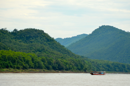 A small boat cruising down the Mekong. Lush mountains are in the background.