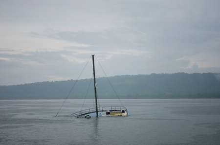 A half-sunken yacht is in a bay, its mast rising up into the overcast sky. Some children are swimming nearby. Tree-covered hills can just be seen through the mist. Stock Photo