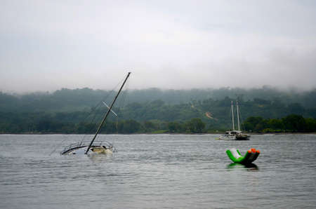 A large floating water toy is near a half-sunken yacht. A catamaran is in the distance. The sky is overcast. Behind are forest covered hills.