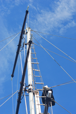 The mast of shot, complete with rigging, is seen against a blue sky. There are a few faint white clouds. A rope ladder stretches to the top of the mast.
