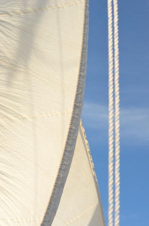 A cream sail on a yacht is edged with grey. Two ropes run beside the sail. The background sky is blue.