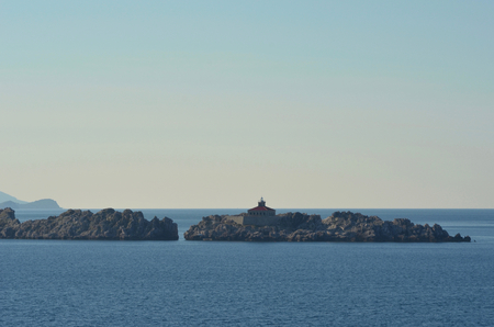 The red roof and light of a light house rise above an island of rocks. The rocks are surrounded by ocean. The sky is clear.