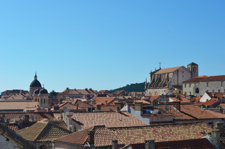 A view over the terracotta tiles covering the roofs of Dubrovnik. Some washing can be seen. The cathedral is to one side. The sky is blue. Stock Photo