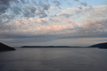 A bank of grey clouds have caught the last colours of sunset. The water below, and surrounding hills, are dark. The sky still has patches of blue.