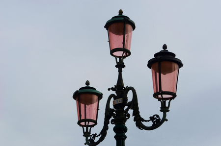An old-style lamp post of black iron, with three lamps. Each has pink glass. The sky behind is overcast, as dusk approaches.