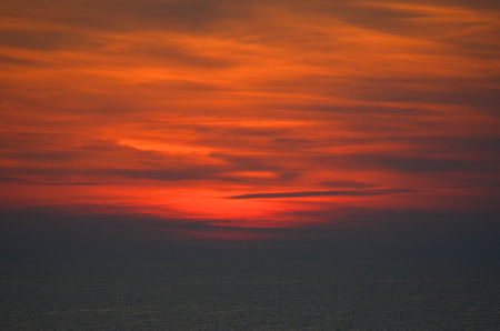 Sunset has turned the sky orange, patterned with dark clouds. Below the clouds, a dark sea can just be seen. Stock Photo