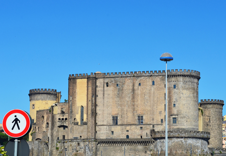 The stone walls of the Castle Nuovo, Naples, rise against a clear blue sky. A red and black pedestrian sign is prominently displayed, and a street lamp makes a contrasting modern feature.