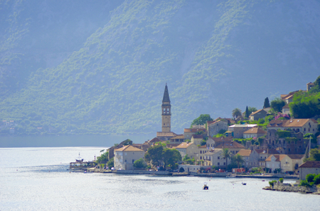 A small town on the Bay of Kotor. The bells of a church steeple are visible against a backdrop of forest-covered mountains. Some people are swimming, and a traditional yacht is in port. Stock Photo