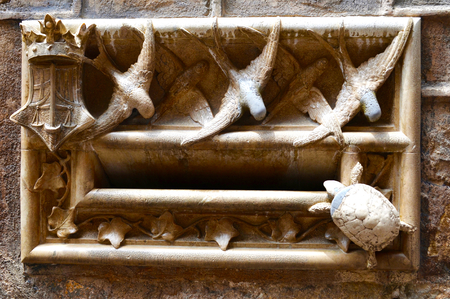 Elaborate stonework around a letter box in a brick wall, which includes twists and a small turtle. A stone vine also wraps around the opening.