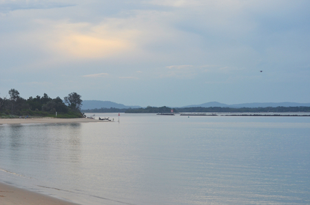 Dusk is falling over an inlet where a river flows to the sea. The sky is cloudy, and islands and rocks divide the inslet is into channels. Trees cover the foreshore. A man is fishing off the beach. Stock Photo