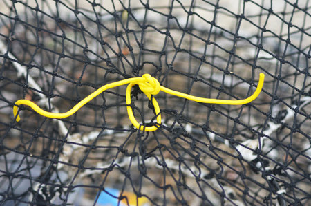 A hole in a fishing net has been repaired by a yellow plastic tie. The net is spread out, and the wire frame can be seen. Stock Photo