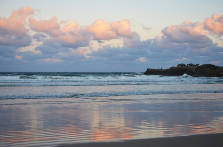 Clouds at sunset, ranging from light pink to purple. The colours are reflected in the water on the beach below. To one side is a rocky shelf, where two men are fishing.
