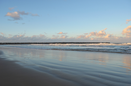 Waves are rolling onto a empty beach past a stone breakwater. The sky is blue, with clouds changing colour with the sunset. These colours are relfected in the water and wet sand. Stock Photo