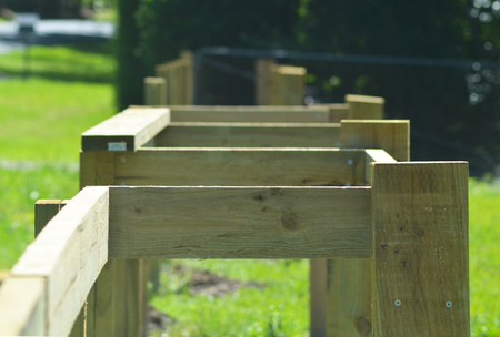 A wooden fence is being built. It consists of horizontal and vertical posts, many still to be put in place. The backgroound is of a green lawn, and a metal fence.