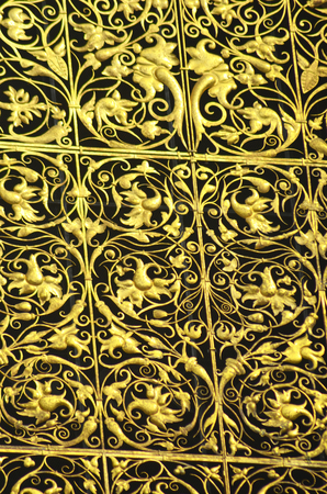 Golden plants twist around one another in exquisite detail on a decorative panel. Stock Photo