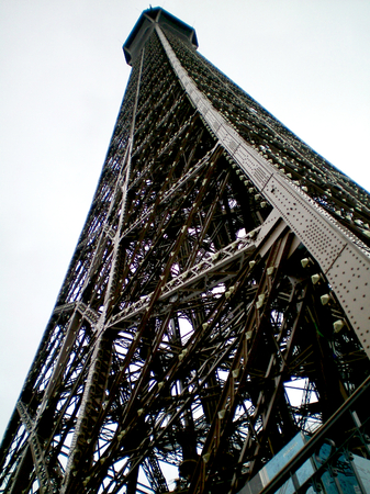 A view of the Eiffel Tower from below, so that the tower soars against a cloudy sky.