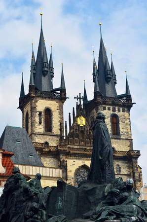 A balck statue of Jan Hus stands outside the Church of Our Lady of Tyn, Prague. The church is of brown stone with black turrets. The sky is blue with white clouds. Stock Photo