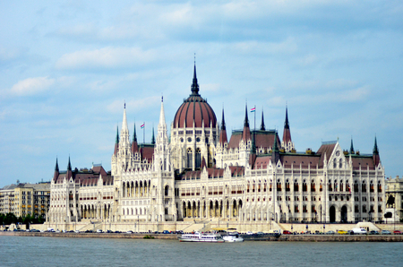 A daytime view of Budapests Houses of Parliment, as seen from the water. Tour boats and buses have gathered on the wharf. The sky is blue with white clouds.