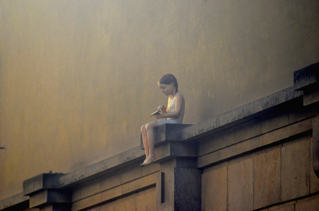 A painted statue of a young girl sitting on a wall of a house. She has what looks like a paper plane in her hands, and is bare-foot. The wall is in shades of brown.