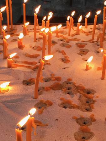 Orange candles have been used as offerings at a shrine. They have been placed in a tray of sand. Melted wax is on the sand, around holes from previous candles. The wall behind the candles is dark.
