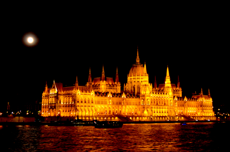 The Houses of Parliment in Budpaest appear gold under lighting. A full moon with a halo is above the historic building. Some boats are on teh Danube. Stock Photo