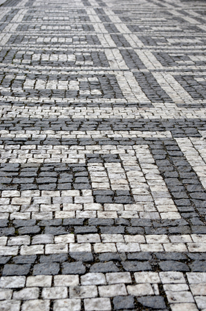 A walkway of light and dark grey cobblestones form a geometric pattern. Stock Photo