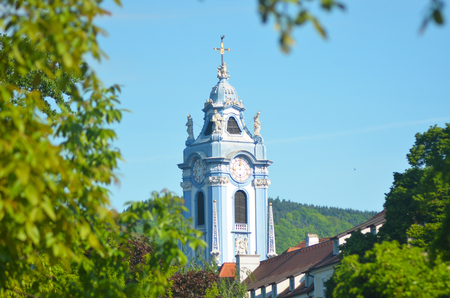 The ornate blue steeple of a church rises against a blue sky. Surrounding buildings can just be seen through a cluster of trees. Forest covered hills are in the background.