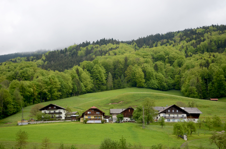 Typical wooden houses in the Austrian alps. They are three stories and have sloping roofs. Behind them are green hills covered with forest. The sky is grey. Editorial