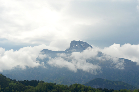 A mountain peak rises above some clouds. Snow can be seen on the peak. Grey clouds are above the mountains. Tree-covered hills are in the foreground. Stock Photo