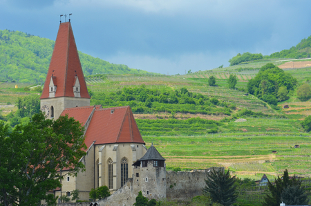 An old church is in a valley, with a vine covered hillside behind it. The church has a red roof and steeple, and high arched windows. An old stone wall with a guard tower is in front of it. Stock Photo