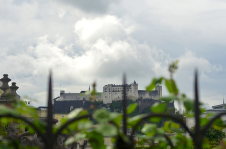 Salzburg Castle is seen in the distance through the iron-work of a rose-covered fence. The roses are still in bud. The sky is overcast.