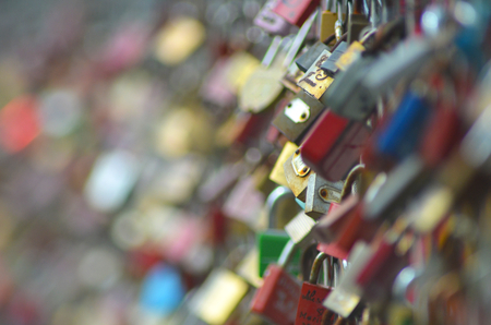 Hundreds of padlocks on a love-lock bridge. Only the padlocks are visible. Only a few are in focus due to the short depth of field. Stock Photo