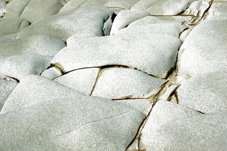 Weathered stones painted to give a textured effect. The stones are shades of white through to grey, with large cracks. Stock Photo