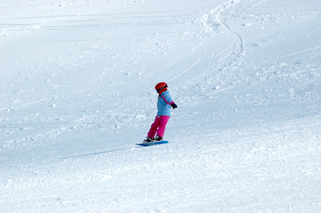 A child is seen side-on, their face covered with a helmet and turned away from the camera. They are snowboarding down a deserted mountain. Tracks from other skiers can be seen.