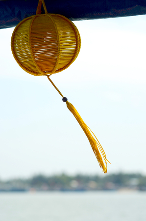 A Vietnamese woven yellow lanten hangs from a wooden beam. Its long tassle is swaying in the breeze. In the background is a bay, with a distant headland with houses. Фото со стока