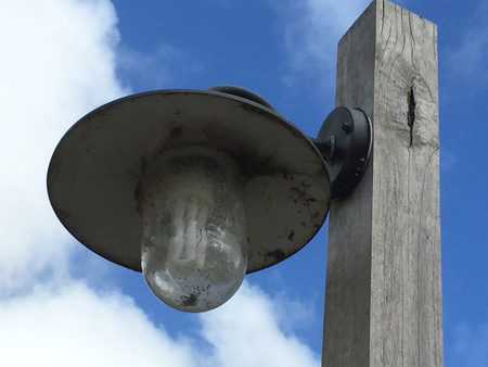 A black metal light is attached to a wooden pole. The bulb is clearly visible, and both are covered with cobwebs. Behind is a blue sky with white clouds.