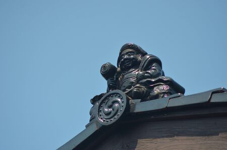 A blackened terracotta statue of a buddha is on the top of a temple roof. He is sitting on some cushions, and is holding a scroll in one hand. He is sitting on the point of the roof, which is covered with black tiles. A clear blue sky is behind him.
