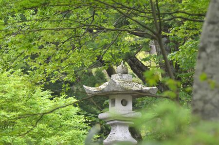 An old stone lantern is surrounded by green trees in a forest in Japan.