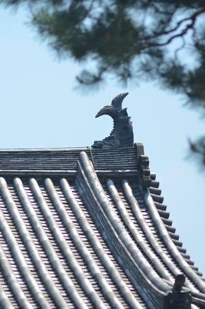 A stone fish is on the roof of a Japanese temple, which is covered with traditional tiles. The fish is resting on its head with its tail raised in the air. The sky is clear. A tree frames the upper corner.